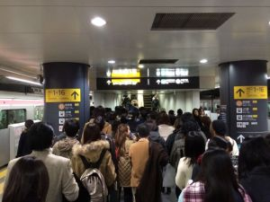 The crowd funnels its way up the sole UP escalator on a subway platform in Shibuya station.